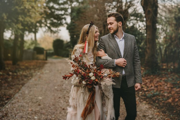 Bride in Sara Lage Wedding Dress  and Verbena Madrid Headdress Holding a Dried Flower Bouquet and Groom in Grey Wool Blazer Arm in Arm