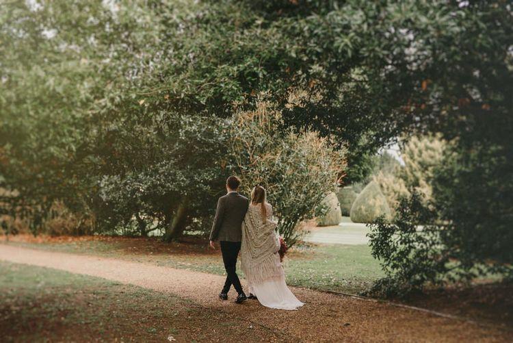 Bride in Sara Lage Wedding Dress  and Wool Shawl and Groom in Grey Wool Blazer Arm in Arm