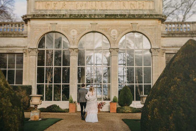 Bride in Sara Lage Wedding Dress and Wool Shawl and Groom in Grey Wool Blazer Standing Outside Their Orangery Wedding Venue
