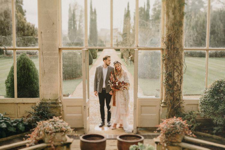 Bride in Sara Lage Wedding Dress and Wool Shawl and Groom in Grey Wool Blazer Entering Their Orangery Wedding Venue