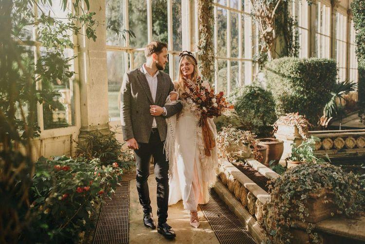 Bride in Sara Lage Wedding Dress and Wool Shawl and Groom in Grey Wool Blazer Inside Their Orangery Wedding Venue