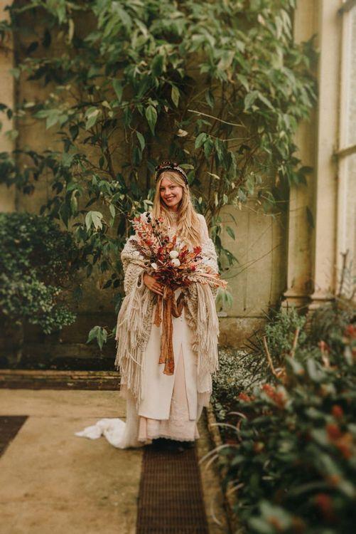 Boho Bride in Sara Lage Wedding Dress and Wool Shawl Holding a Dried Flower Wedding Bouquet
