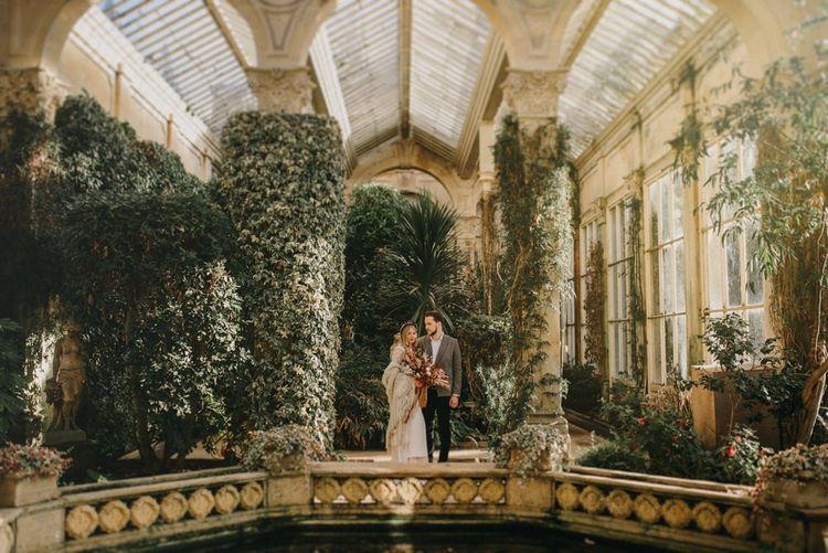 Boho Bride and Groom Embracing in an Orangery