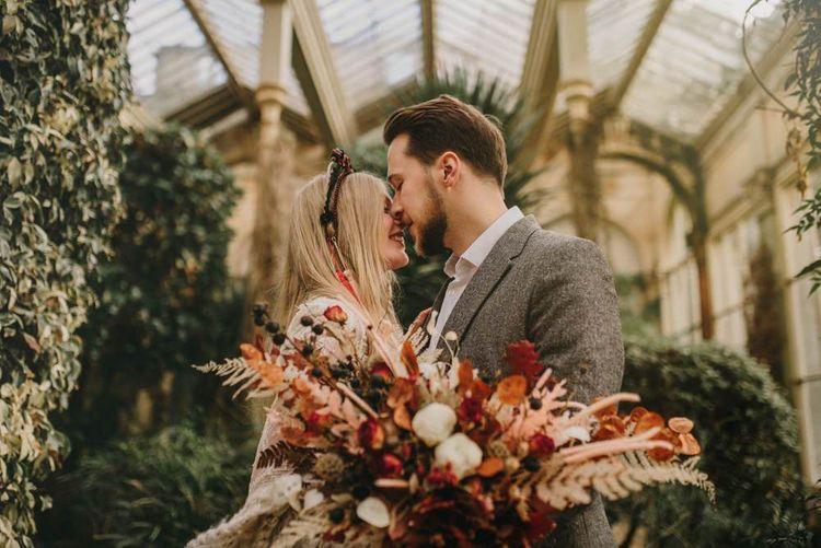 Boho Bride and Groom Kissing in their Orangery Wedding Venue