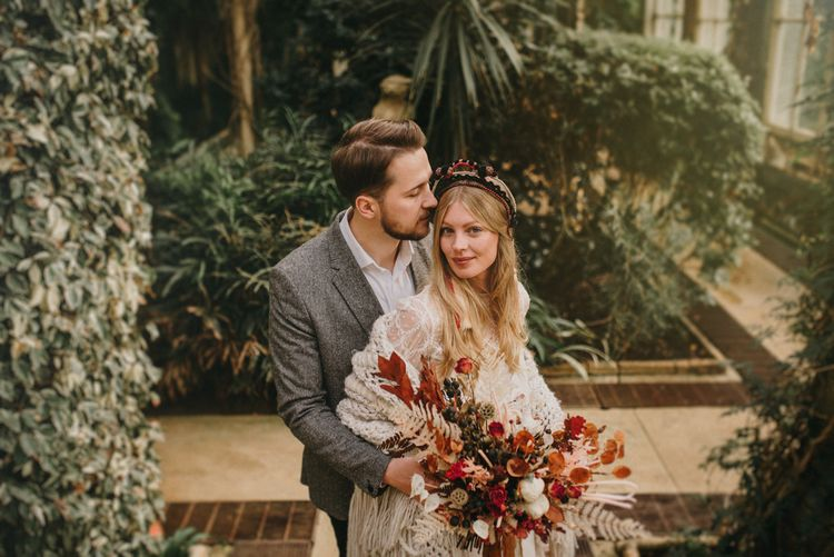 Groom in Grey Wool Blazer Embracing His Bride in a Verbena Madrid Headdress Holding a Dried Flower Bouquet
