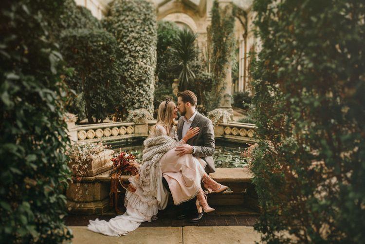 Boho Bride Sitting on Her Grooms Knee in an Orangery