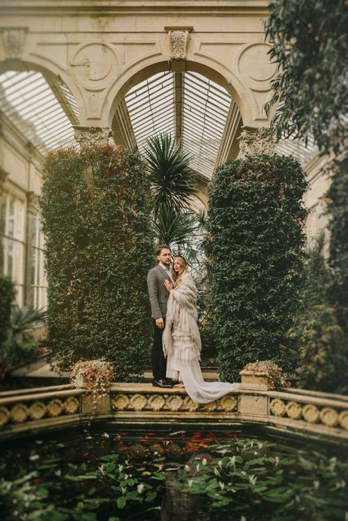 Boho Bride and Groom Standing Next to a Water Feature in an Orangery