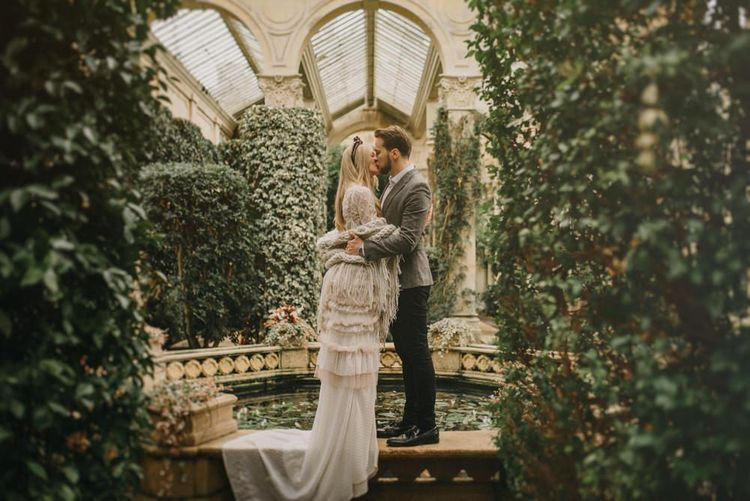 Boho Bride and Groom kissing in an Orangery