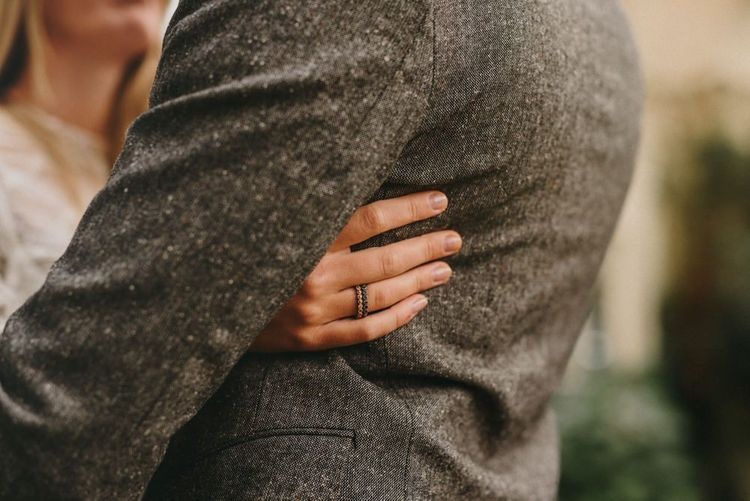 Bride Putting Her Arm Around Her Groom Showing Off Her Delicate Wedding Band