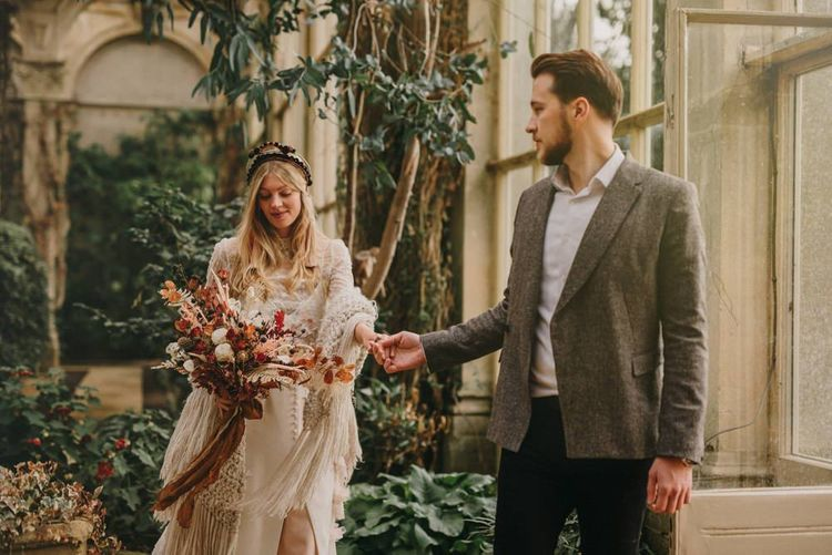 Groom in Grey Wool Blazer Holding His Brides Hand in a Sara Lage Wedding Dress and Verbena Madrid Headdress, Holding a Dried Flower Bouquet