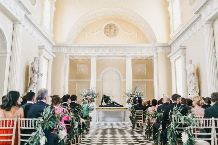 Wedding Ceremony at Syon Park | Groom in Navy Lanvin Tuxedo and Black Burberry Shoes | Burgundy Bow Tie | Huge Urns of Cafe au Lait Dahlias, David Austin Roses, Hydrangeas, Delphinium, Cosmos, Eucalyptus and Olive | Stunning Syon Park Wedding with Quill Stationery Suite | Nancy Ebert Photography