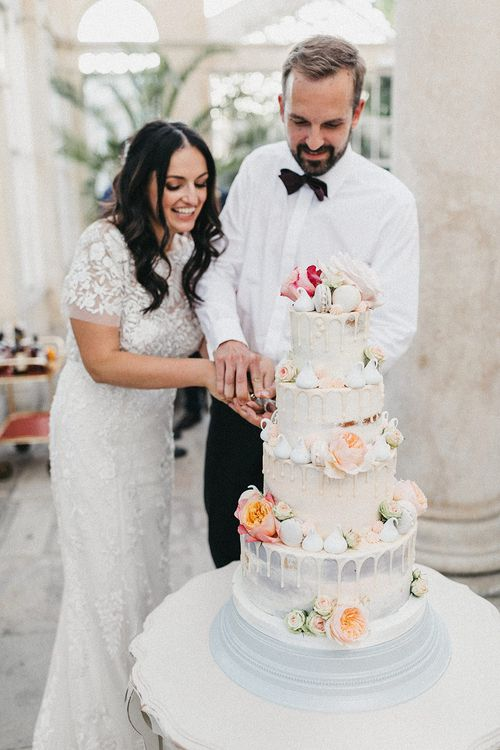 Cutting of Cake | Semi Naked Four Tier Drip Cake | Bride in Hermione de Paula Wedding Gown with Short Sleeves and Personalised Embroidery | Groom in Navy Lanvin Tuxedo and Black Burberry Shoes | Burgundy Bow Tie | Stunning Syon Park Wedding with Quill Stationery Suite | Nancy Ebert Photography
