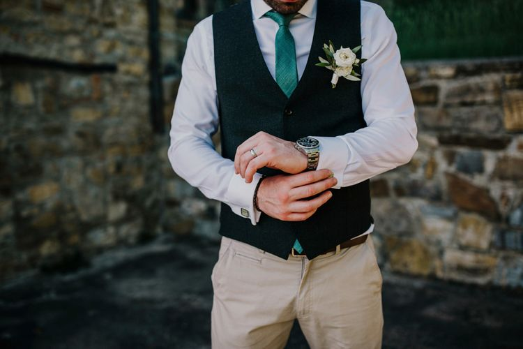 Groom in waistcoat with green tie and flower buttonhole
