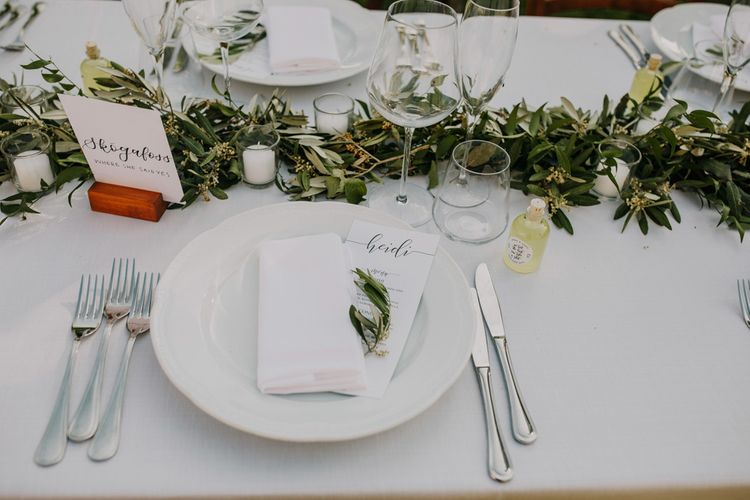 Wedding table place setting with foliage table runner at wedding with bridesmaid dresses in mint green
