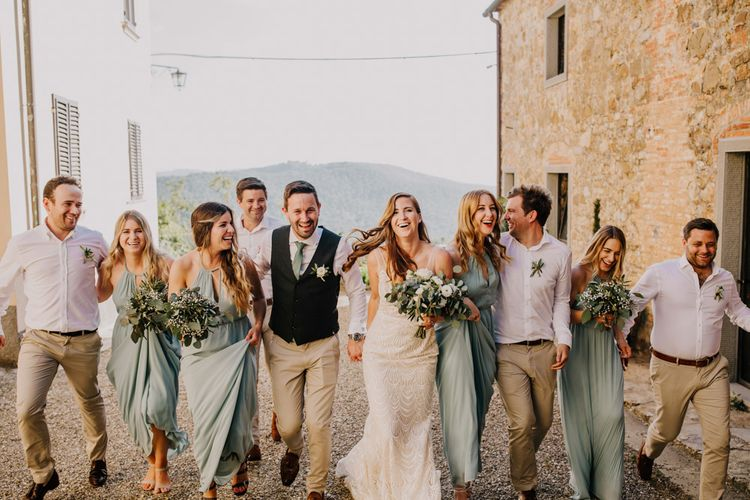 Groomsmen in cream trousers and bridesmaid dresses in mint green