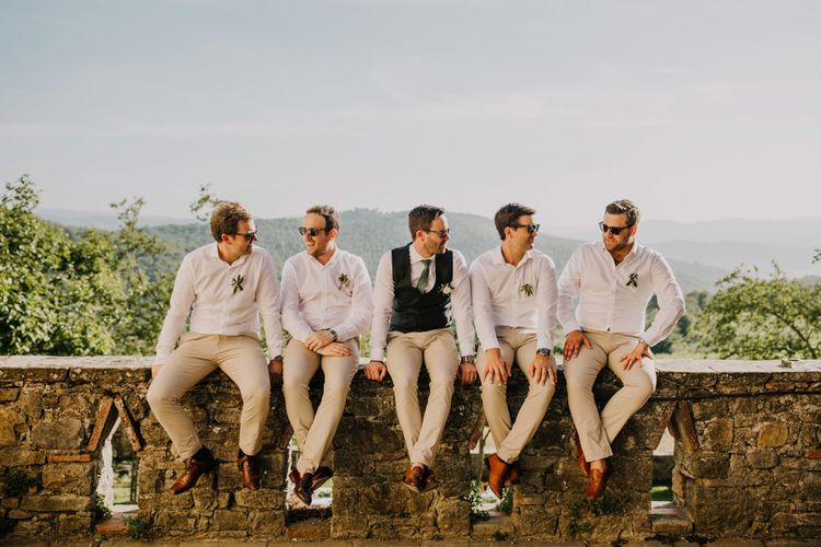Groomsmen in matching cream trousers and bridesmaid dresses in mint green