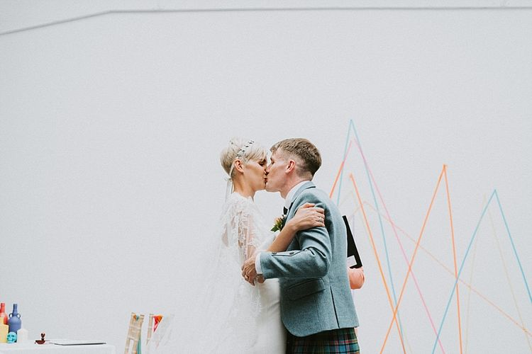 Bride in Sassi Holford Wedding Dress and Lace Cape and Groom in Tartan Kilt and Tweed Jacket  Kissing