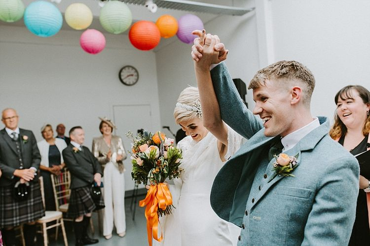 Bride in Sassi Holford Wedding Dress and Lace Cape and Groom in Tartan Kilt and Tweed Jacket  Just Married