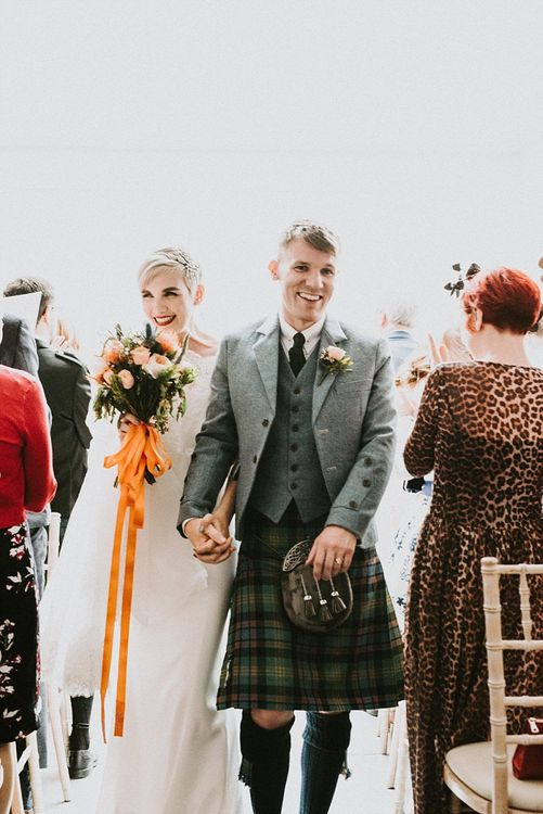 Bride in Sassi Holford Wedding Dress and Lace Cape and Groom in Tartan Kilt and Tweed Jacket Walking Up the Aisle as Husband & Wife