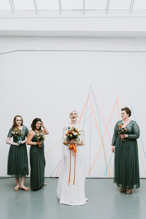 Bride in Sassi Holford Wedding Dress and Lace Cape with Bridesmaids in Grey Sequin Maya Dresses