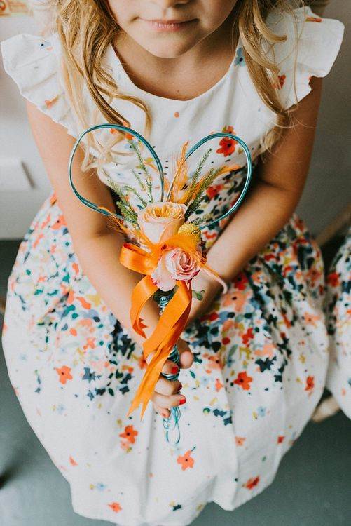 Flower Girl in Floral Print Dress Holding Small Posey of Flowers