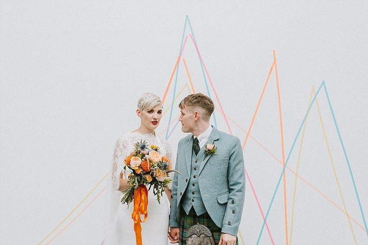 Bride in Sassi Holford Wedding Dress and Lace Cape and Groom in Tartan Kilt and Tweed Jacket Standing in Front of Bright Geometric Wall Art