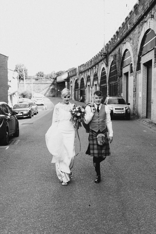 Black and White Portrait of Bride in Sassi Holford Wedding Dress and Lace Cape and Groom in Tartan Kilt and Tweed Jacket