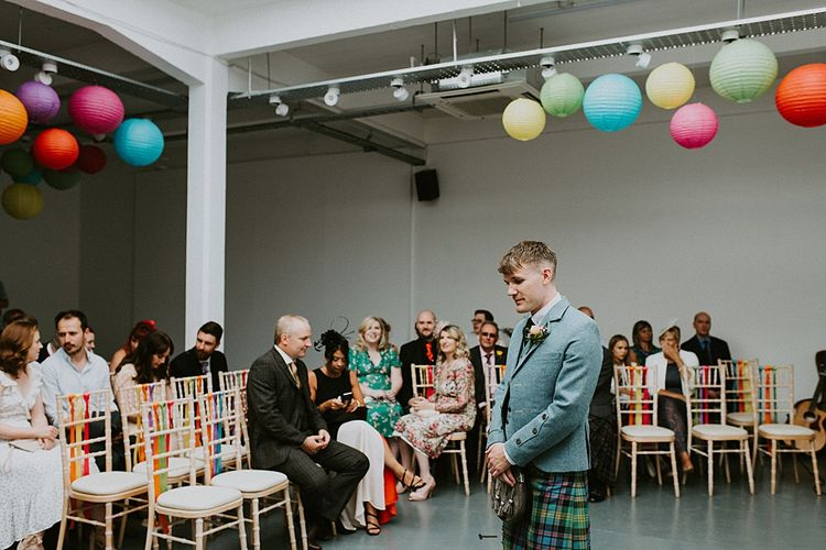 Groom in Tartan Kilt Waiting at the Altar with Colourful Paper Lanterns and Ribbon Wedding Ceremony Decor