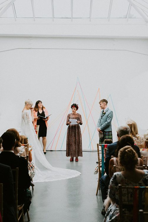 Warehouse Wedding Ceremony with Colourful Geometric Patterned Backdrop