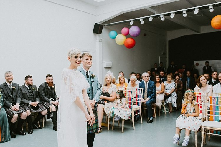 Bride in Sassi Holford Wedding Dress and Lace Cape and Groom in Tartan Kilt and Tweed Jacket at Wedding Ceremony