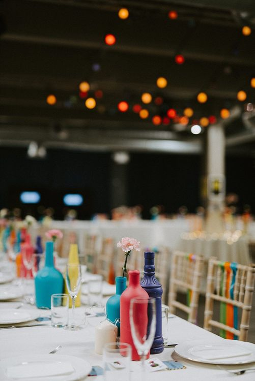 Clusters of colourful Spray Painted Bottles as Wedding Reception Table Decor