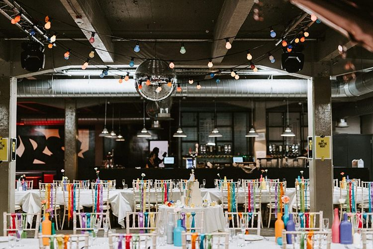 Wedding Warehouse Reception Decor with Colourful Festoon Lights and Ribbon Chair Decor