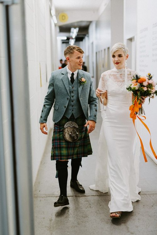 Bride in Sassi Holford Wedding Dress and Lace Cape and Groom in Tartan Kilt and Tweed Jacket