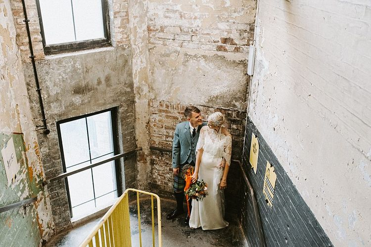 Bride in Sassi Holford Wedding Dress and Lace Cape and Groom in Tartan Kilt and Tweed Jacket with Industrial Backdrop