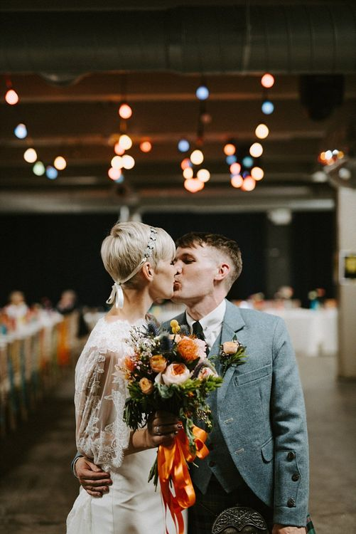 Bride in Sassi Holford Wedding Dress and Lace Cape and Groom in Tartan Kilt and Tweed Jacket Kissing at Wedding Reception