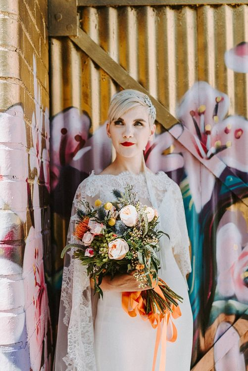 Bride in Sassi Holford Wedding Dress and Lace Cape Holding Peach and Orange Wedding Bouquet