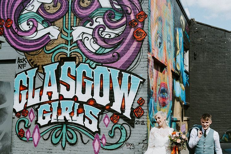 Bride in Sassi Holford Wedding Dress and Lace Cape and Groom in Tartan Kilt and Tweed Jacket Standing in Front of Street Art