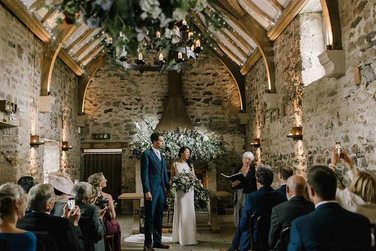 Wedding Ceremony | Bride in Racerback Pronovias Wedding Dress | Groom in Navy Blue Morning Suit | Pastel Bridal Bouquet | Floral Displays Hanging from Ceiling | Healey Barn Countryside Wedding with Wild Flowers and Bride in Pronovias | Georgina Harrison Photography
