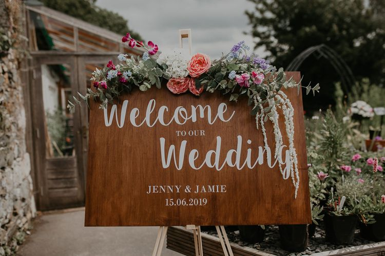 Wooden wedding welcome sign with flower decoration