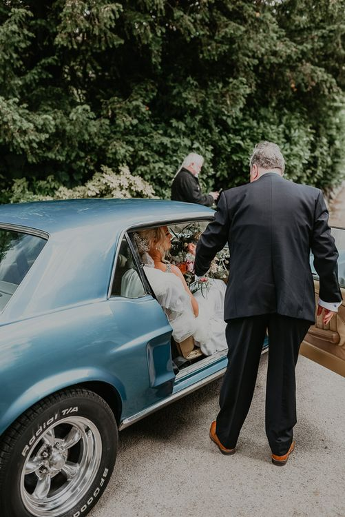 Bride arrives in blue wedding car with father