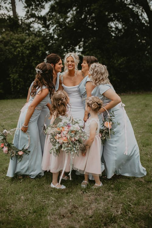 Blue bridesmaid dresses and pink flower girls with hoop bouquets
