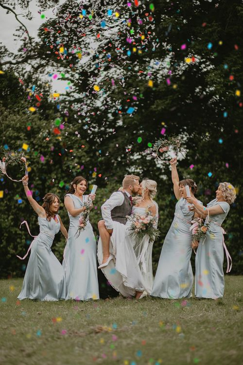 Bride and groom kiss between blue bridesmaids with hoop bouquet