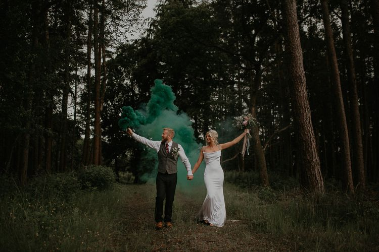 Blue smoke bomb at Cumbria wedding with bride in embroidered veil