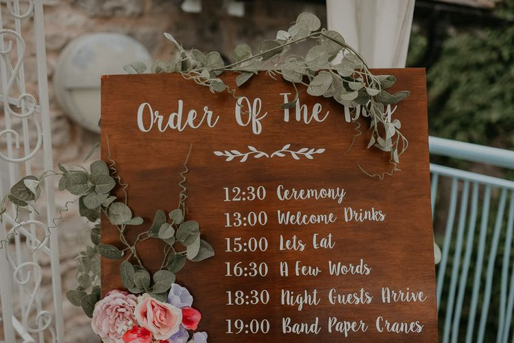Wooden wedding order of the day with pastel wedding flowers
