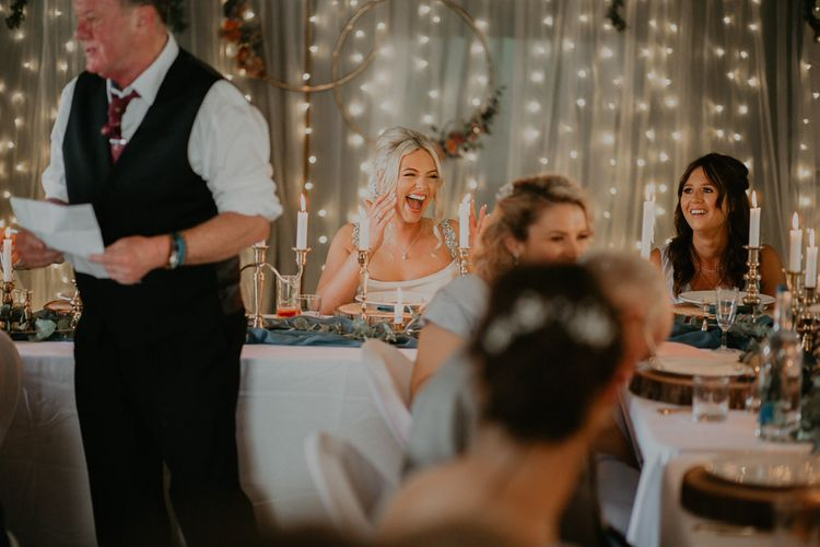 Bride wearing embroidered veil enjoys wedding speeches with fairy light backdrop