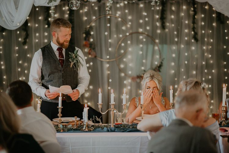 Bride gets emotional during  wedding speeches with fairy light backdrop