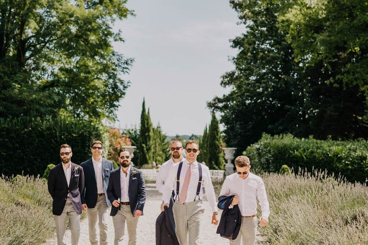 Groom in Navy Jacket, Grey Trousers and White Shirt with Pink Tie from Suit Supply   Outdoor Seating Area and Macaroon Tower at French Chateau Wedding   Lush Imaging