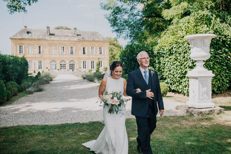 Bride in Lace Boat Neck Pronovias Wedding Dress with Keyhole Back and Fishtail Train   Fingertip Length Veil   Bridal Bouquet of Blush and White Flowers with Foliage   Father of the Bride in Navy Three-Piece Suit with Blue Tie   Entrance of the Bride at Chateau La Durantie, Dordogne   Outdoor Seating Area and Macaroon Tower at French Chateau Wedding   Lush Imaging