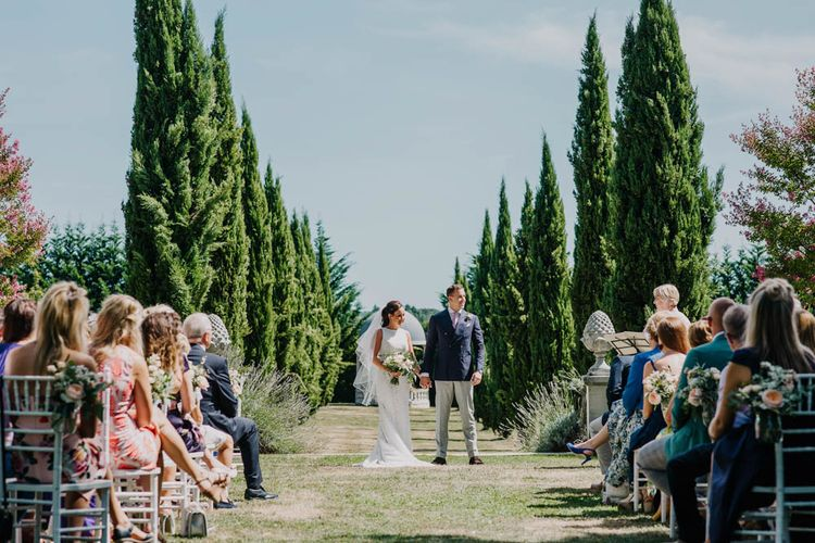 Bride in Lace Boat Neck Pronovias Wedding Dress with Keyhole Back and Fishtail Train   Fingertip Length Veil   Bridal Bouquet of Blush and White Flowers with Foliage   Groom in Navy Jacket, Grey Trousers and White Shirt with Pink Tie from Suit Supply   Outdoor Wedding Ceremony at Chateau La Durantie, Dordogne   Outdoor Seating Area and Macaroon Tower at French Chateau Wedding   Lush Imaging