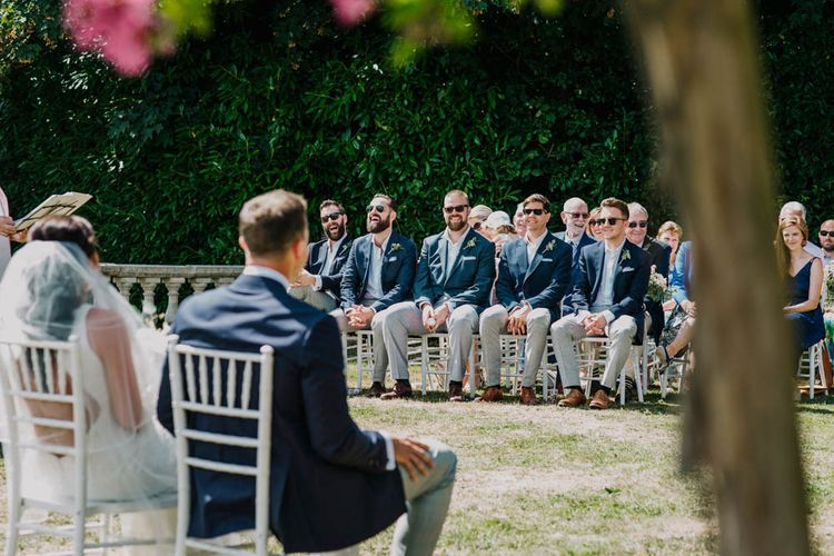 Groomsmen in Navy Jackets and Grey Trousers   Bride in Lace Boat Neck Pronovias Wedding Dress with Keyhole Back and Fishtail Train   Fingertip Length Veil   Groom in Navy Jacket, Grey Trousers and White Shirt with Pink Tie from Suit Supply   Outdoor Wedding Ceremony at Chateau La Durantie, Dordogne   Outdoor Seating Area and Macaroon Tower at French Chateau Wedding   Lush Imaging